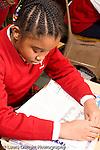 K-8 Parochial School Bronx New York Grade 4 girl reading from handout in class vertical