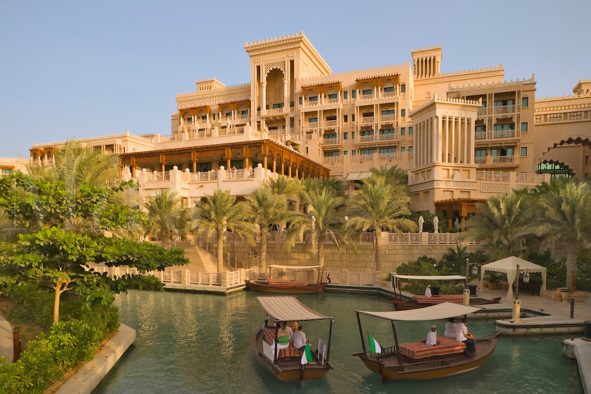 Dubai.  Al Qasr Hotel, built in the style of a Moroccan palace, seen over one of the Madinat Jumeirah?s canals with  abras,  water taxis.  ..