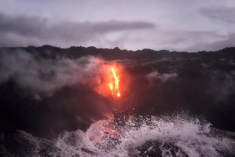 Lava and waves crashing at sunrise. Hawai'i Volcanoes National Park, HI