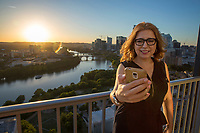 Happy smiling, attractive woman wearing glasses in casual dress taking selfies on high-rise skyscraper balcony, Lady Bird Town Lake and Austin, Texas skyline backdrop at sunset.