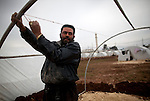 Abdallah Hamed from Aleppo fixes his family's tent after it was broken by the wind at Azaz Camp, just inside the Syrian border with Turkey, Feb. 22, 2013. According to administrators, this camp holds roughly 9,000 to 10,000 internally displaced persons (IDP's). Some food is provided by a Turkish humanitarian organization, and Qatar Red Crescent provided tents. There is very little electricity, and no running water. The UN Refugee Agency has reported a sharp increase in refugees fleeing Syria for neighboring countries in the first months of 2013.