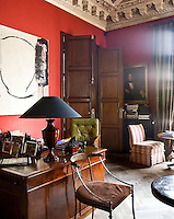 Rows of photographs line the polished desk in the office, under an ornate plasterwork ceiling