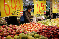 A shoppers picks fruit at a Carrefour Supermarket in Shanghai, China. According to a recent report, China has surpassed the United States in total consumption of every basic food, energy, and industrial commodity except oil, as well as goods such as television sets, refrigerators and mobile phones. However the per capita income for China is only roughly one seventh of that of the U.S..19 Feb 2005