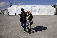 Pictured: A couple of refugees having just been given food Friday 26 February 2016<br /> Re: Hundreds of refugees have been given temporary shelter at the Stefanakis Army Camp in the Schisto area of Athens, Greece.