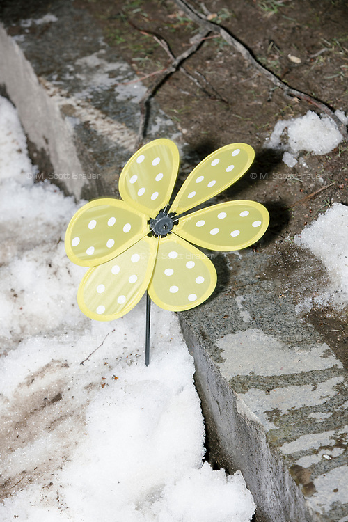 A pinwheel in the shape of a flower stands in a snowbank next to a curb as people gather during the March For Our Lives protest and demonstration in Boston Common in Boston, Massachusetts, USA, on Sat., March 24, 2018. The march was held in response to recent school gun violence.