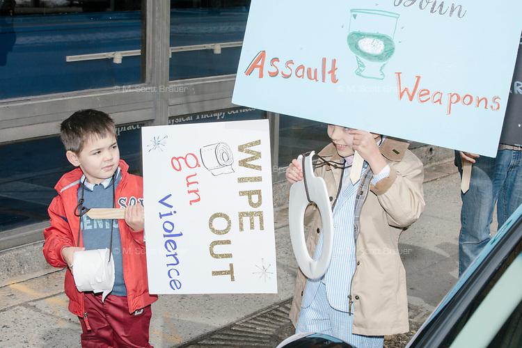 """Brothers Emmett, age 5, (left) holding a sign reading """"Wipe out gun violence"""", and Ronan, age 7, holding a sign reading """"Flush down assault weapons,"""" as they take part in the March For Our Lives protest, walking from Roxbury Crossing to Boston Common, in Boston, Massachusetts, USA, on Sat., March 24, 2018, in response to recent school gun violence."""