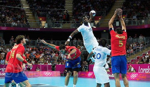 08 AUG 2012 - LONDON, GBR - Luc Abalo (FRA) of France (top in white) leaps to shoot during the men's London 2012 Olympic Games quarter final match against Spain at the Basketball Arena in the Olympic Park, in Stratford, London, Great Britain .(PHOTO (C) 2012 NIGEL FARROW)