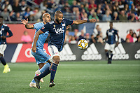 FOXBOROUGH, MA - SEPTEMBER 29: Heber #9 of New York City FC comes in to tackle Andrew Farrell #2 of New England Revolution during a game between New York City FC and New England Revolution at Gillettes Stadium on September 29, 2019 in Foxborough, Massachusetts.