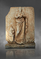 Roman Sebasteion relief  sculpture of Hygieia, Aphrodisias Museum, Aphrodisias, Turkey.  Against a grey background.<br /> <br /> Hygieia, the goddess of Health, hold a flat bowl (phiale) from which she feeds a snake. The snake is wound twice around her forearm. A plump naked child sits on a square pedestal. Hygieia was the daughter of the healing god Asklepios, with whom she is paired here