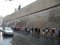 Crowds queue in the rain outside of the Vatican Museum, Italy