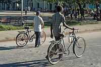 Two men walking with their bikes alongside Parque Vidal in Santa Clara, Villa Clara, Cuba.
