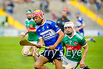 Seamus O'Halloran of St Brendan's on a solo run been chased by Sean McGrath of Crotta in the County Senior Hurling Championship quarter final