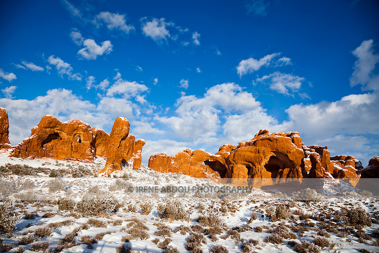 Double Arch looms in the distance.  Fantastic rock formations and arches sculpted over thousands of years by wind, rain, and other forces of erosion dot the winter landscape of the Windows Section of Arches National Park in southern Utah.
