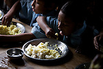 Young boys eat traditional Nepali food, dal bhat, lentils and rice with their hands at an orphange in Pokhara, Nepal.