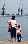 A mother and child watch boys swimming in the Royal Victoria Dock, Newham. The dock would be one of the watersport facilities used if London's bid for the 2012 Olympic Games is successful.
