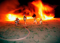 oil fire with fire fighters