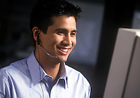 Young speaking through headset phone while consulting a computer monitor.