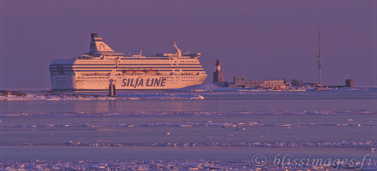 Silja Liner leaves Helsinki and passes Harmaja Lighthouse while breaking through the pastel colours of winter ice in the Gulf of Finland