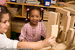 Preschool 4-5 year olds block area children playing with wooden blocks two girls setting sign on top of structure horizontal