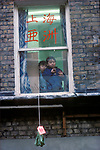 Fortune Cookies. Chinese New Year Soho community London Two small children watch from window as good luck charm bag is lowered 1970s UK
