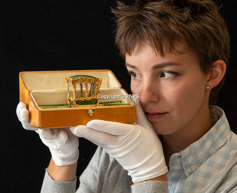 BNPS.co.uk (01202 558833)<br /> Pic: PhilYeomans/BNPS<br /> <br /> Georgina Bouzyk from the Cotswold Auction Co carefully hold the Russian gem...<br /> <br /> In from the cold - £500,000 Romanov treasure is hot property at Cotswold auction.<br /> <br /> An exquisite Faberge antique believed to have been made for the Russian Royal family over 100 years ago sold yesterday for a whopping £500,000...over 5 times it's estimate.<br /> <br /> The model of a sedan chair by the iconic Russian jewellers was one of the state treasures seized and sold off by the communist regime following the Russian Revolution.<br /> <br /> It was first sold at high-end Anglo-Russia antique dealers Wartski in London in 1929, where it was bought by a K.W Woollcombe-Boyce for only £75.<br /> <br /> The ornate item, crafted from Jadeite, gold, rock crystal and mother of pearl, has remained in the family ever since and is now being sold by a direct descendant of Mr Woollcombe-Boyce.<br /> <br /> Experts from the Cotswold Auction Company gave the small Russian antique a pre-sale estimate of only £100,000, but always anticipated it could go for much more than that.