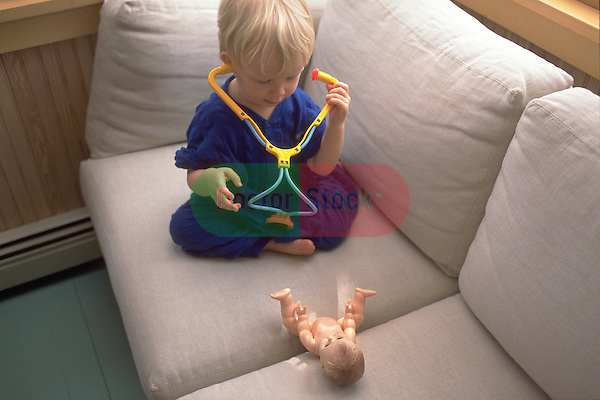 toddler girl examines toy doll with stethoscope