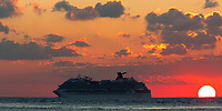 Beautiful sunset on cruise ship, with the sun as an enormous white ball on the Caribbean Sea in a colorful, cloudy orange sky, Cozumel Island, Mexico