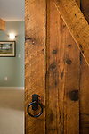 A sliding door made from reclaimed barn wood adds a touch of history to a newly-remodeled basement.