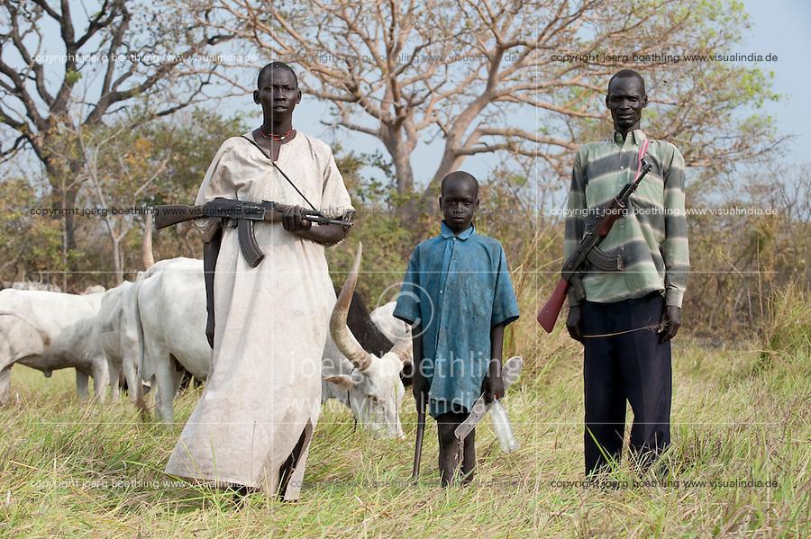 SOUTH SUDAN, Rumbek, young Dinka man protect the Zebu cattle of his family with AK-47 rifle against Nuer cattle raider / SUED SUDAN Rumbek , Matur ein 18 jaehriger Dinka Hirte schuetzt Zeburinder vor Viehdiebstaehlen durch Nuer mit seinem Kalaschnikow Maschinengewehr, kleinerer Junge Makuei 11 Jahre