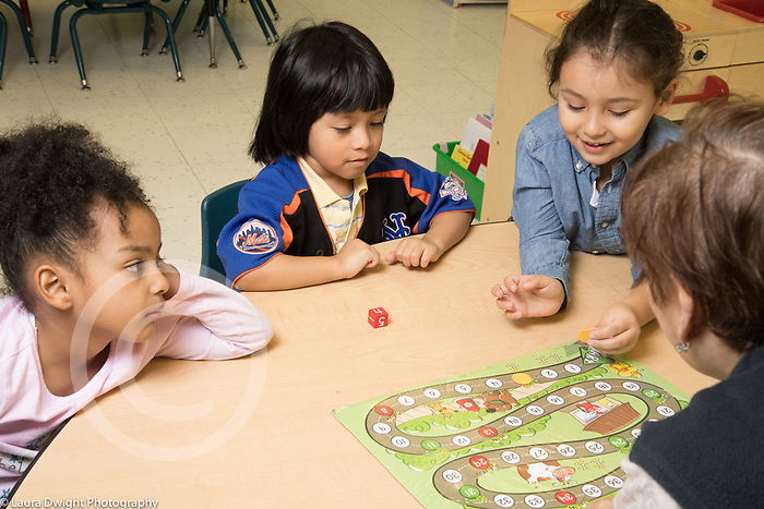 Education Preschool 4 year olds group of children playing board game involving counting and using die, taking turns