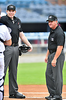 Umpires Mitch Leikam and Rusty Griffin before a game between the Greenville Drive and the Asheville Tourists on July 20, 2021 at McCormick Field in Asheville, NC. (Tony Farlow/Four Seam Images)