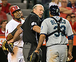 Home plate umpire separates Los Angeles Angels Erick Aybar and Seattle Mariners catcher, Henry Blanco.