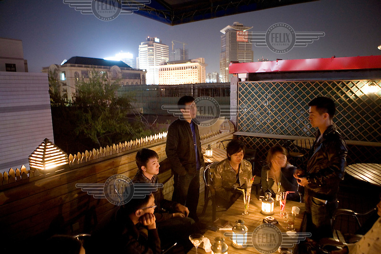 Friends spend the night out in a bar in the popular Sanlitun street.