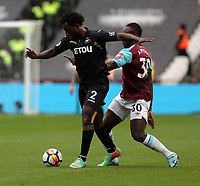 Wilfried Bony of Swansea City (L) charges past Michail Antonio of West Ham during the Premier League match between West Ham United v Swansea City at the London Stadium, London, England, UK. Saturday 30 September 2017