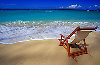 Beach chair on a tropical sunny Hawaiian beach with blue water and white clouds