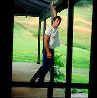 Man hanging from porch beam seen through screen door