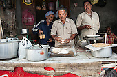 Amritsar, Punjab, India. Three men working at a street food stall, preparing chai tea and chapati bread.