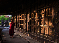 A Buddhist Monk walking through an old Teakwood Monastery in Mandaly, Myanmar, Burma.
