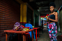 An Afro-Colombian girl peels off a cooking banana in a street restaurant in the market of Bazurto in Cartagena, Colombia, 12 December 2017. Far from the touristy places in the walled city, a colorful, vibrant labyrinth of Cartagena's biggest open-air market sprawls to the Caribbean seashore. Here, in the dark and narrow alleys, full of scrappy stalls selling fruit, vegetables and herbs, meat and raw fish, with smelly garbage on the floor and loud reggaeton music in the air, the African roots of Colombia are manifested.