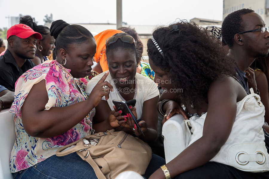 Passengers Looking at Cell Phone Pictures on the Dakar-Goree Ferry, Senegal.