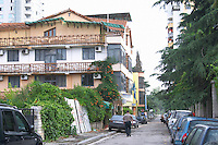 Street scene with a man walking in the middle of the street from the part of the city called The Block that used to be reserved for party dignitaries during the communist era. Apartment house with wooden balconies. Tirana capital. Albania, Balkan, Europe.