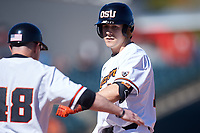 Oregon State Beavers Ryan Ober (18) is congratulated by the first base coach after hitting a single during an NCAA game against the New Mexico Lobos at Surprise Stadium on February 14, 2020 in Surprise, Arizona. (Zachary Lucy / Four Seam Images)