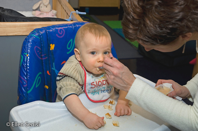 MR / Schenectady, NY.Schenectady Day Nursery / private non-profit daycare center / Infant Class.Teacher feeds infant (boy 10 months) food as he sits in high chair..MR: Coo4.© Ellen B. Senisi