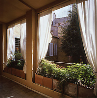 Simple white cotton curtains are draped the length of the terrace, while tentative new shoots from square terracotta containers, bask in the Spring sunshine
