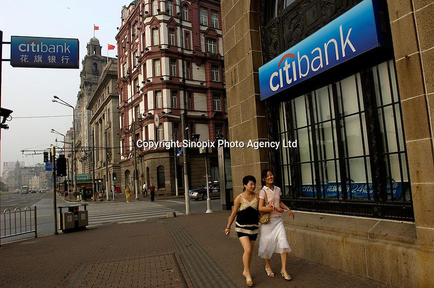 Two girls walk past a Citibank branch in Shanghai Bund. .