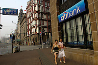 Two girls walk past a Citibank branch in Shanghai Bund. .