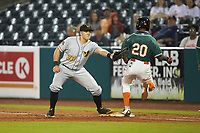West Virginia Power first baseman Mason Martin (23) squeezes the ball in his glove as Samuel Castro (20) of the Greensboro Grasshoppers steps on the bag at First National Bank Field on June 1, 2018 in Greensboro, North Carolina. The Grasshoppers defeated the Power 10-3. (Brian Westerholt/Four Seam Images)