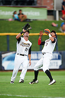 Quad Cities River Bandits left fielder Pat Porter (31) and shortstop Kristian Trompiz (3) get under a shallow fly ball during a game against the Bowling Green Hot Rods on July 24, 2016 at Modern Woodmen Park in Davenport, Iowa.  Quad Cities defeated Bowling Green 6-5.  (Mike Janes/Four Seam Images)