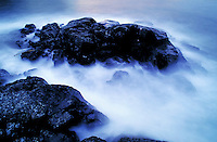 WAVES BREAKING ON ROCKS IN NANOOSE BAY.MOTION, TIDE, BLUE WATER, OCEAN, GEORGIA STRAIGHT. BRITISH COLUMBIA CANADA VANCOUVER ISLAND.