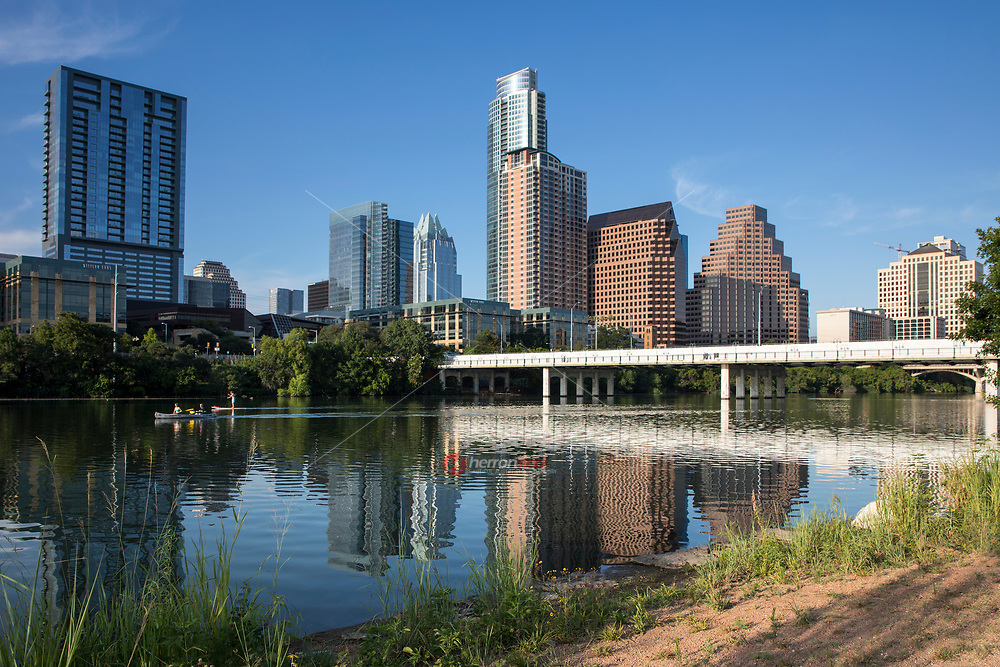 kayaking and Stand up paddle boarding (SUP) is a favorite pastime of water activities on Lady Bird Lake with Austin Skyline backdrop on a beautiful summer's day.